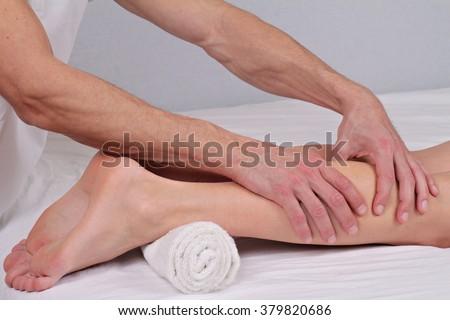Woman enjoying leg massage.Therapist applying pressure on female leg. - stock photo