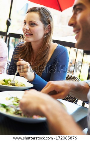 Woman Enjoying Meal At Outdoor Restaurant With Friends - stock photo