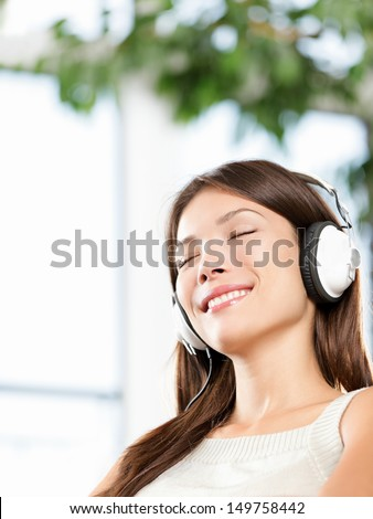 Woman enjoying music in headphones at home relaxing. Relaxed girl sitting in sofa listening to music with earphones with eyes closed looking serene, blissful and happy, Mixed race Asian Caucasian, 20s - stock photo