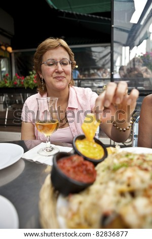 Woman enjoying Nachos and Beer at an Outdoor Cafe - stock photo