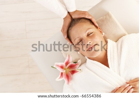 Woman enjoying relaxing head massage in dayspa with closed eyes.? - stock photo