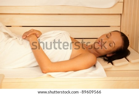 Woman enjoying sauna, lying with eyes closed, relaxing in healthy wellness.?