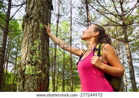 Woman enjoying the beautiful pines travel green forest in Europe.  Ecotourism concept image with happy female hiker. - stock photo