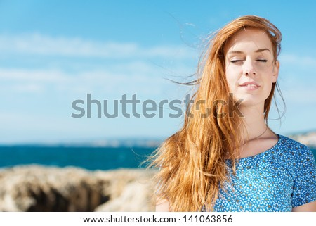 Woman enjoying the peace of summer at the seaside standing in the hot sun with her eyes closed - stock photo