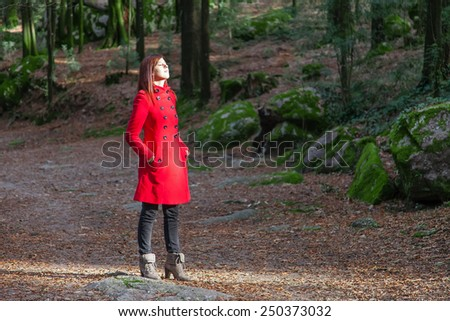 Woman enjoying the warmth of the winter sunlight on a forest wearing a red overcoat - stock photo