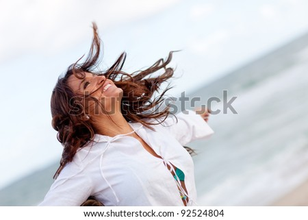 Woman enjoying the windy weather at the beach and relaxing