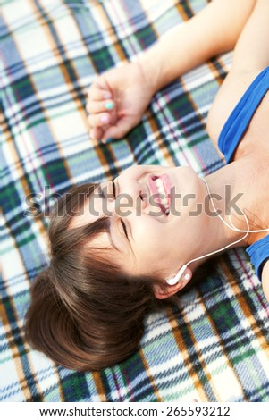 Woman enjoying to music lying on the plaid in the park. Technology is everywhere  - stock photo