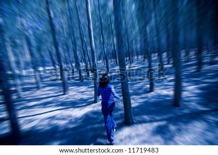 Woman escaping from unrevealed danger through the woods in the night - stock photo