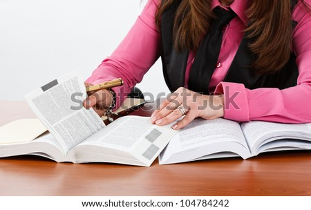 Woman examining books and documents - stock photo