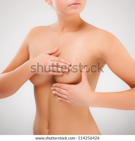 Woman examining breast isolated on white background - stock photo