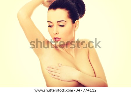 Woman examining breast mastopathy or cancer.