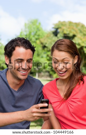 Woman excitedly watches as she is shown something on the friend's mobile phone while sitting in an open park area - stock photo