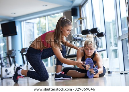 woman exercise and  working out with fitness personal trainer in gym - stock photo