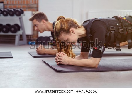 Woman exercises in gym on yoga mat besides man as they both wear ems fitness vest - stock photo