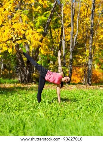 Woman exercises in the autumn forest yoga Ardha chandrasana pose - stock photo