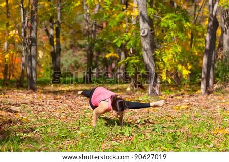 Woman exercises in the autumn forest yoga kaundiniasana pose - stock photo