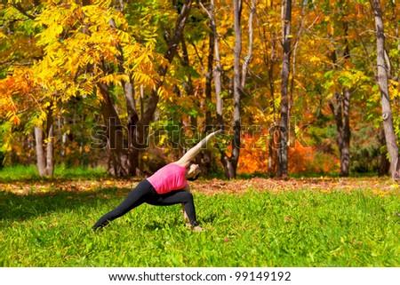 Woman exercises in the autumn forest yoga utthita parshvakonasana pose - stock photo