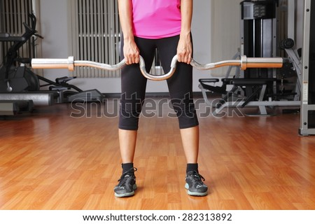 woman exercises with empty bar in gym