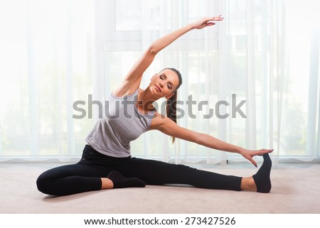 Woman exercising in a bright room  - stock photo