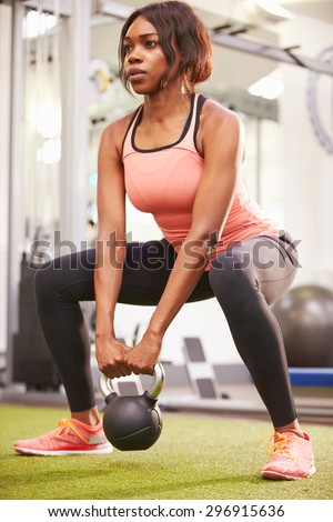 Woman exercising in a gym with a kettlebell weight, vertical - stock photo