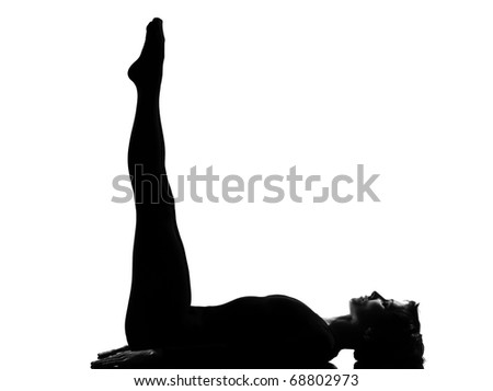 woman exercising lying on back fitness yoga stretching in shadow grayscale silhouette full length in studio isolated white backgroun - stock photo