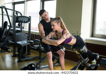 Woman exercising with her fitness instructor at the fitness center