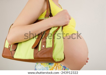Woman expecting a baby holding a bag in her hands. Close up on pregnant belly traveling. - stock photo