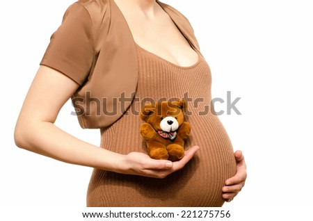 Woman expecting a baby holding a cute teddy bear. Close up on pregnant belly isolated on white. - stock photo