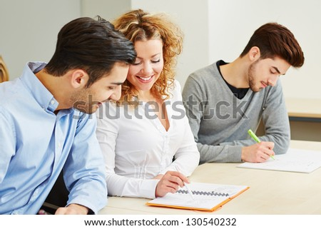 Woman explaining student exercises in university class