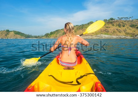 Woman exploring calm tropical bay with limestone mountains by kayak. - stock photo