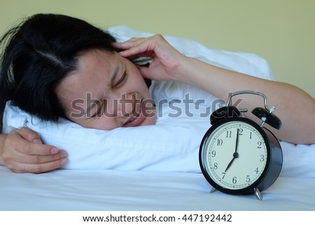 woman extremely annoyed by the alarm clock