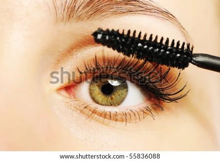 Woman eye with long eyelashes and mascara brush - stock photo