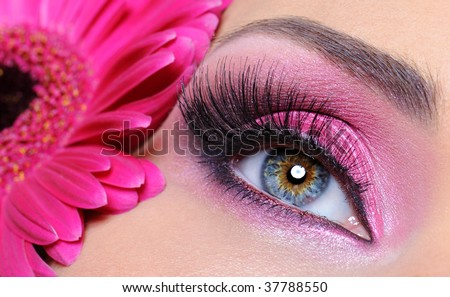 Woman eye with pink make-up and false eyelashes -   gerber flower - stock photo