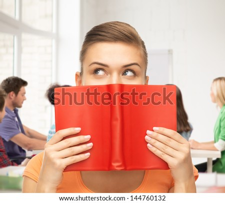woman eyes and hands holding red book at school - stock photo