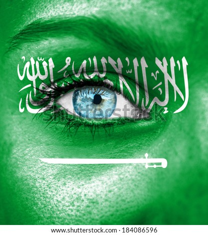 Woman face painted with flag of Saudi Arabia - stock photo