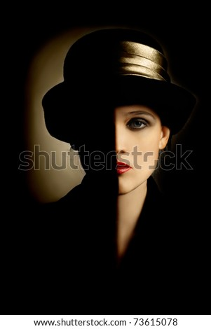 Woman face with black half. Artistic portrait of beautiful woman in black hat - stock photo