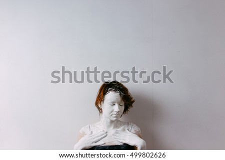 Woman face with cracked skin. Skin of woman is white painted and cracked. Eyes are closed