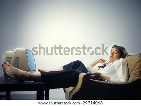 woman falling asleep while she's watching tv - stock photo