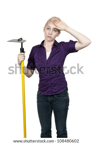 Woman farmer with a hoe in the furrows of a freshly plowed field