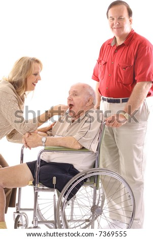 woman feeding elderly man in wheelchair - stock photo