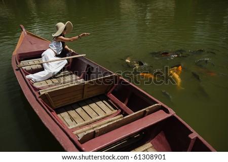 woman feeding goldfish in large pond - stock photo