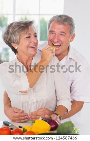 Woman feeding pepper to man in kitchen