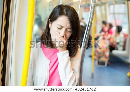 Woman feeling sick inside train compartment - stock photo