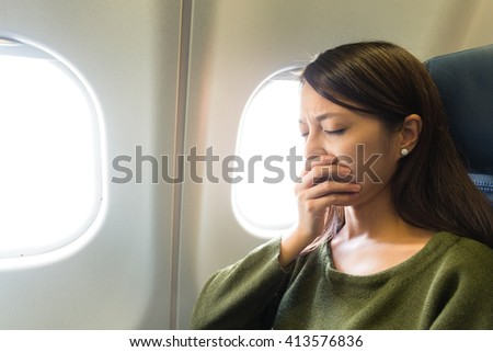 Woman feeling tired on aircraft - stock photo