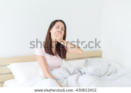 Woman feeling tired on bed - stock photo