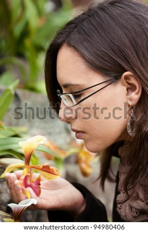 Woman feels the smell of a yellow orchid flower in Spring - stock photo