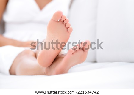 Woman feet closeup - barefoot woman relaxing in sofa. Close up of female feet of young beautiful woman sitting in couch outside. - stock photo