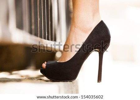 woman feet in black high heel shoes  stand by fence outdoor shot - stock photo