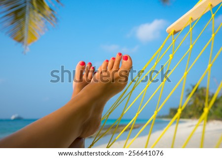 woman feet in hammock on the beach - stock photo
