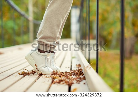 Woman feet in white shoes standing tiptoe on hanging bridge in autumn park. Side view. Outdoors fall season multicolored horizontal image. - stock photo
